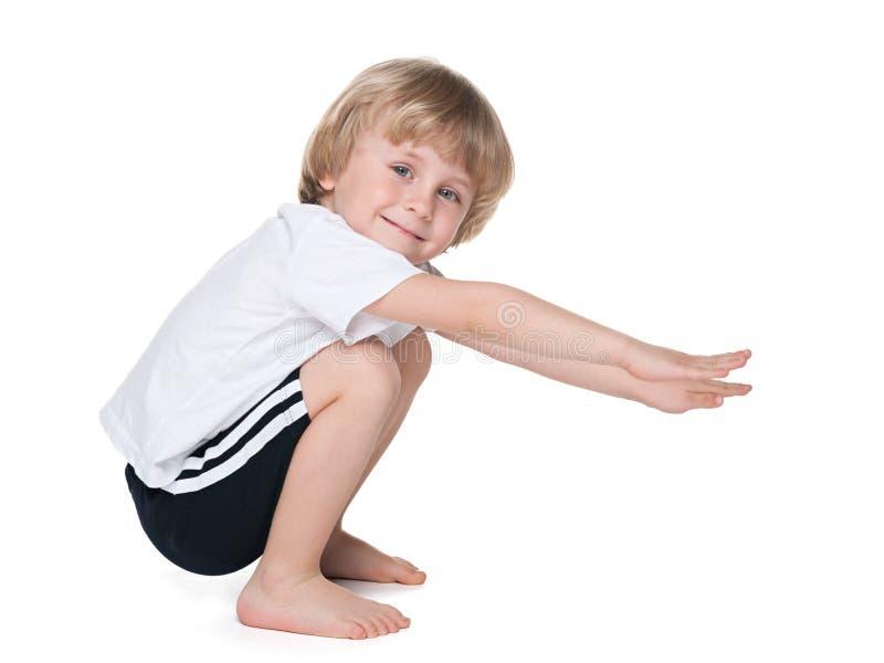 El muchacho preescolar realiza ejercicios foto de archivo