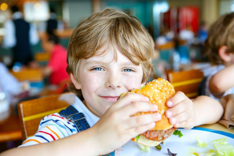 El muchacho preescolar sano lindo come la hamburguesa que se sienta en café al aire libre imagen de archivo libre de regalías