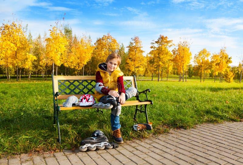 El muchacho puso los rodillos que se sentaban en el banco imagen de archivo libre de regalías