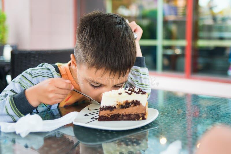El muchacho que comía un punto bajo de la torta dobló sobre la placa en café fotos de archivo