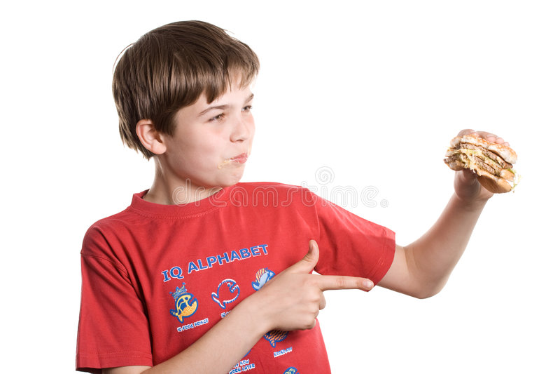 El muchacho que come una hamburguesa. fotografía de archivo