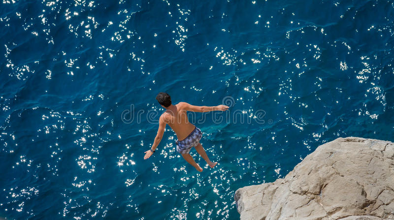 El muchacho que salta de roca en el Mar Egeo foto de archivo libre de regalías