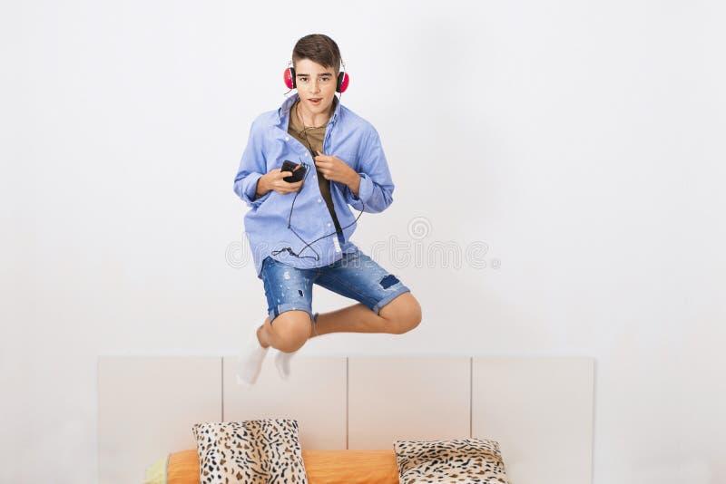 El muchacho que salta en cama fotos de archivo libres de regalías