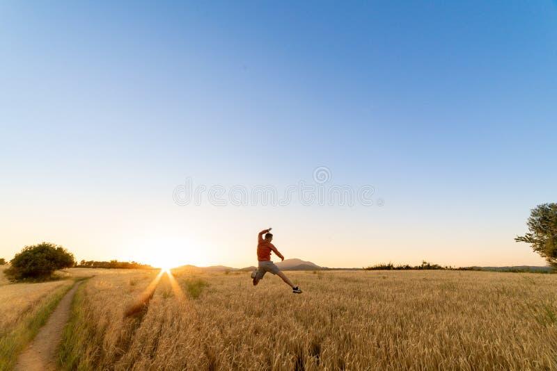 El muchacho que salta en el campo de trigo de a imagen de archivo
