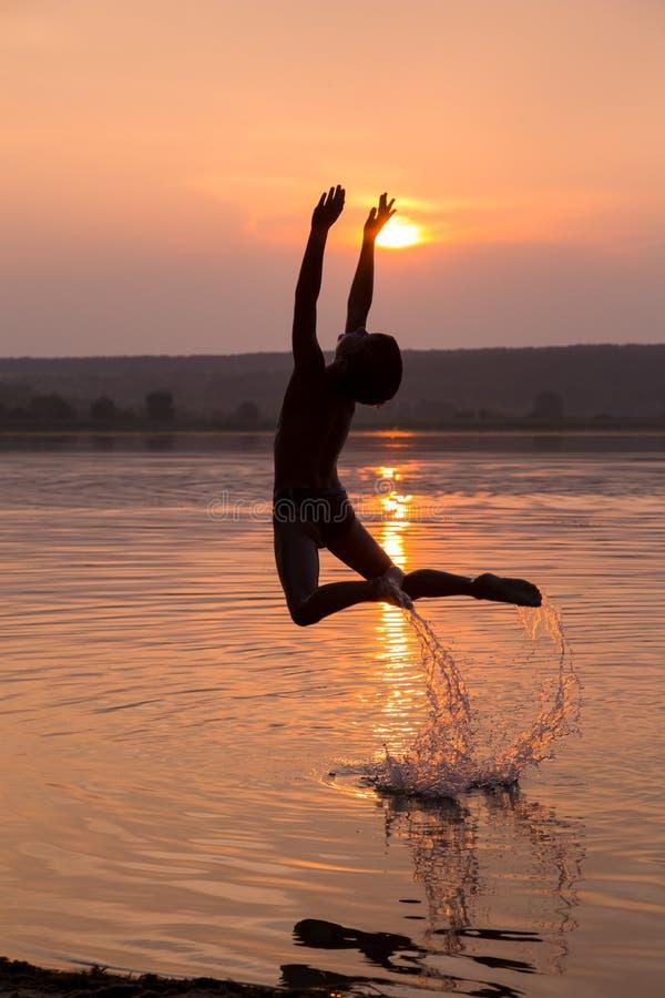 El muchacho que salta en el agua en puesta del sol foto de archivo libre de regalías