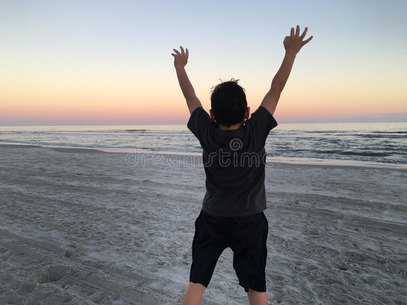 El muchacho que salta en la playa foto de archivo libre de regalías