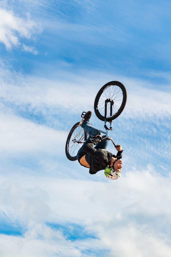 El muchacho que salta un alto aturde gastos indirectos en una bici de montaña El jinete joven en la rueda de su bmx hace un truco imagen de archivo libre de regalías