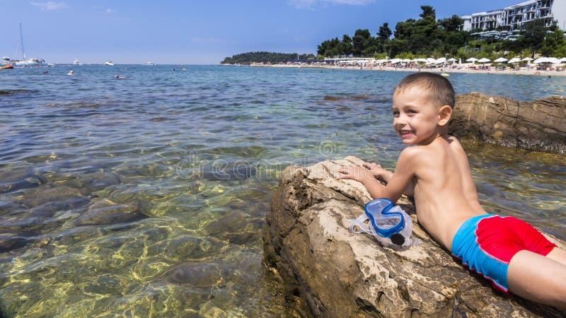 El muchacho que se relaja en la playa imágenes de archivo libres de regalías