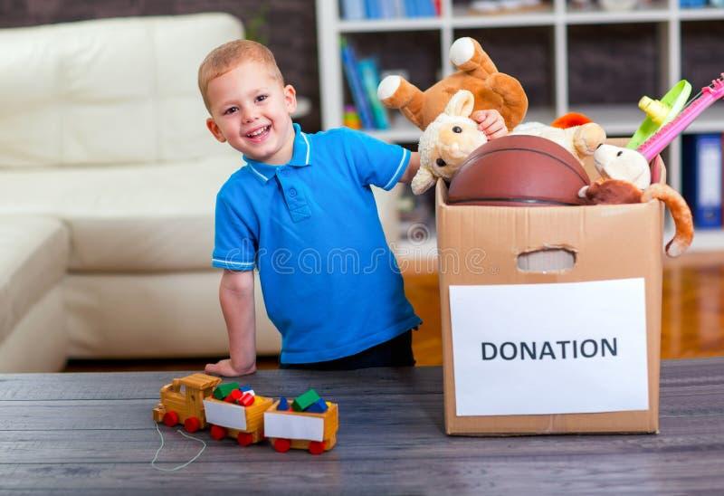 El muchacho que toma la caja de la donación con la materia para dona por completo fotografía de archivo libre de regalías