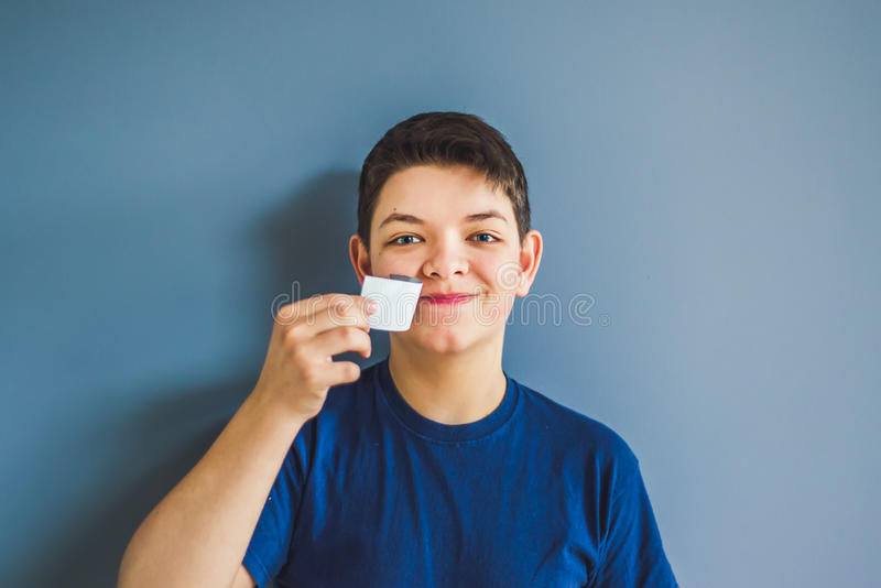 El muchacho rasga apagado una cinta adhesiva de una boca imagenes de archivo