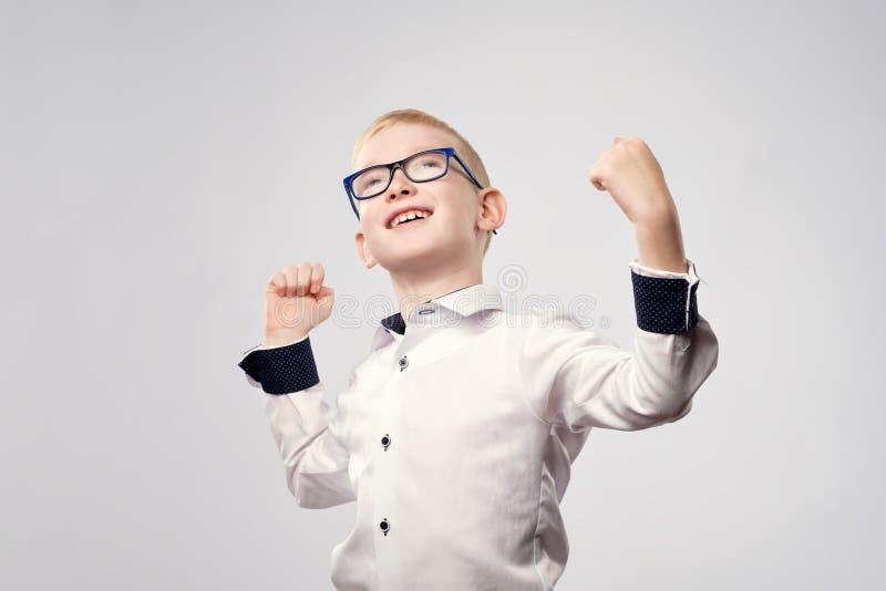 El muchacho rubio caucásico feliz está alegre con triunfo foto de archivo libre de regalías