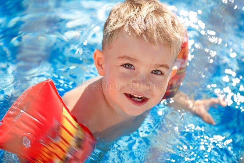 El muchacho rubio encantador se baña en una piscina en las mangas, riendo foto de archivo libre de regalías