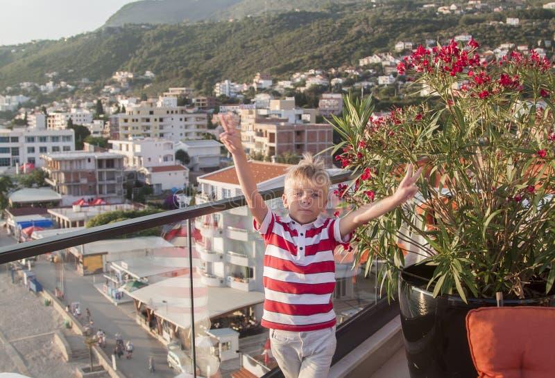 el muchacho rubio mira la cámara y lanza su mano para arriba con un vict imágenes de archivo libres de regalías