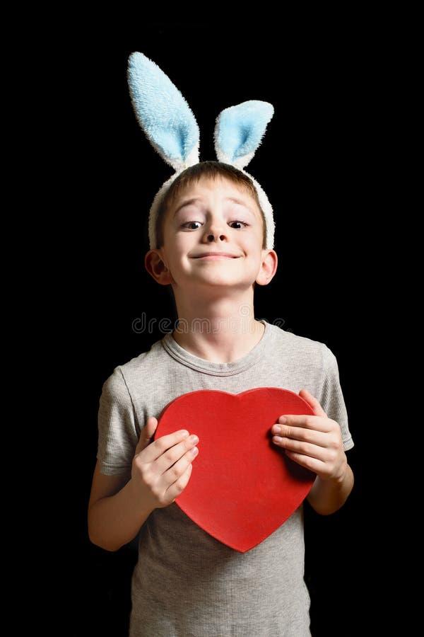 El muchacho rubio sonriente en oídos de las liebres sostiene la caja roja de la forma del corazón en fondo negro Concepto del amo fotos de archivo