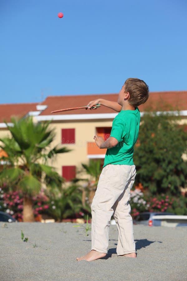 El muchacho sacude encima de la raqueta de la pelota de tenis imagen de archivo libre de regalías