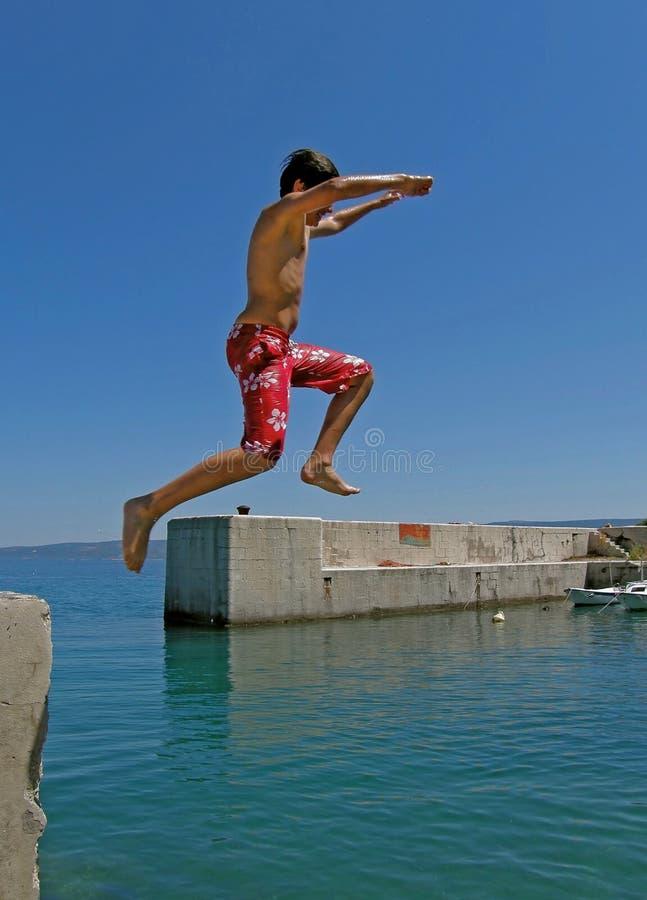 El muchacho salta en el mar fotos de archivo