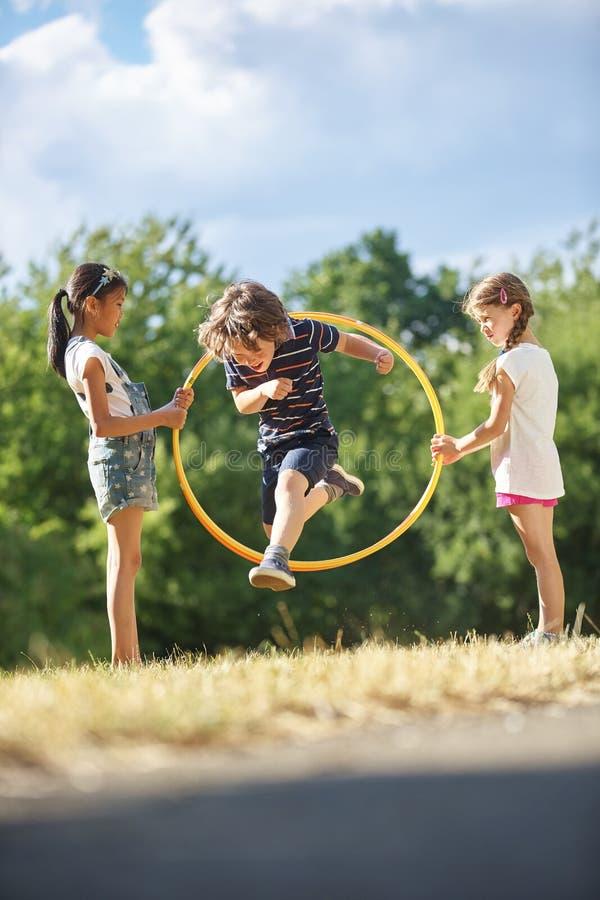 El muchacho salta a través de aro del hula imagenes de archivo