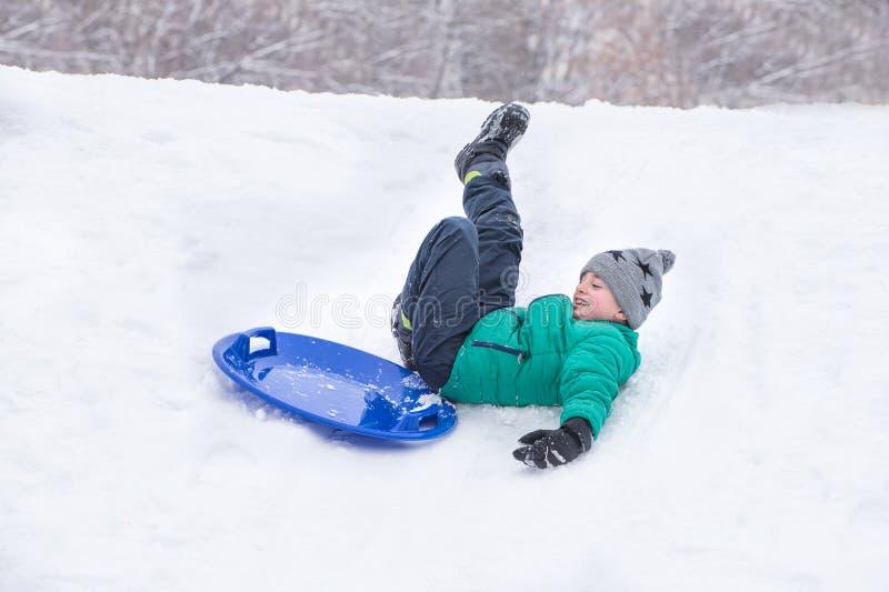 El muchacho se cae balanceo abajo una colina en el platillo de la nieve Modelado dinámico del carácter fotografía de archivo libre de regalías