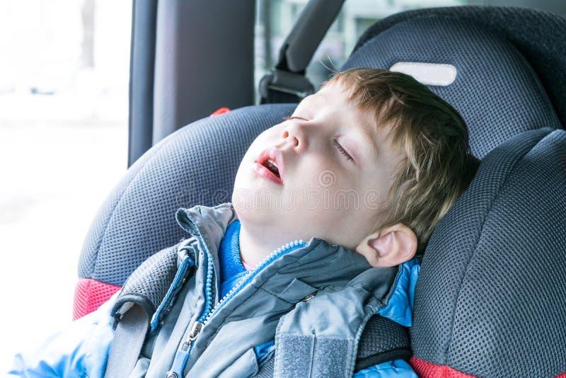 El muchacho se cayó dormido en el asiento del niño del coche imagenes de archivo
