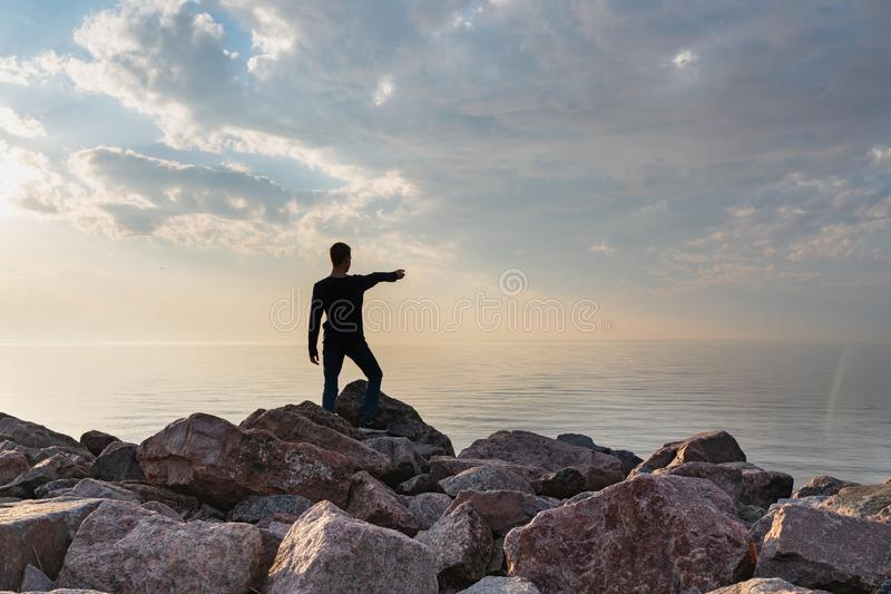 El muchacho se coloca en una playa de piedra en un d?a caliente en la puesta del sol fotos de archivo