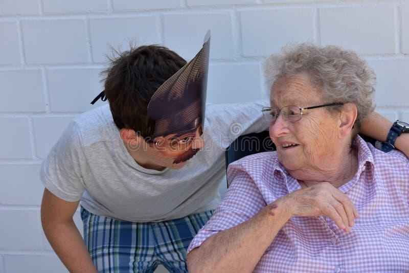 El muchacho se divierte con su abuela foto de archivo