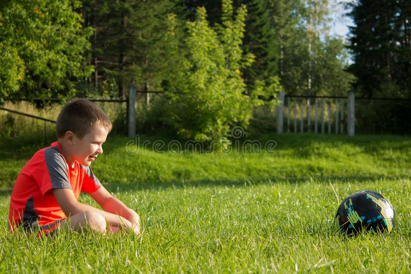 El muchacho se está sentando en la hierba y mira el balón de fútbol fotos de archivo