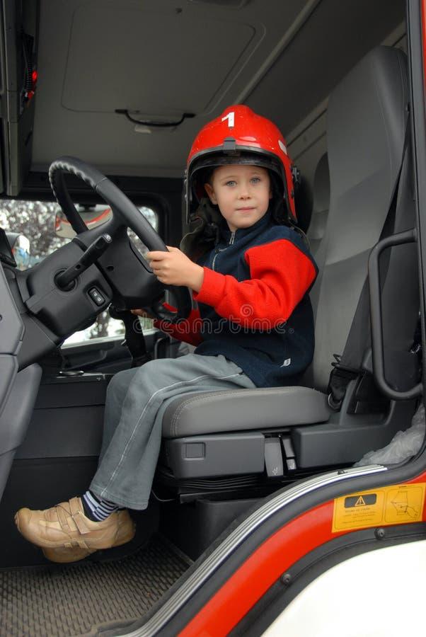 El muchacho se está sentando en un coche de bomberos foto de archivo