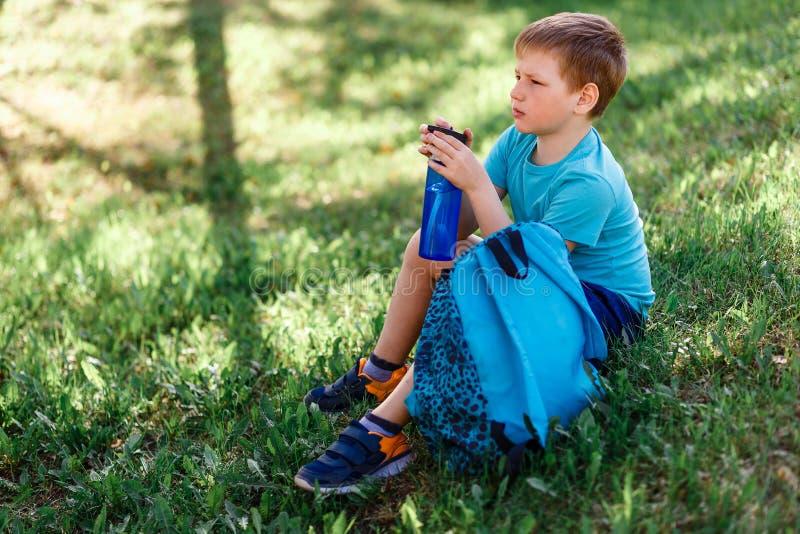 El muchacho se sienta en la hierba con una botella de agua en sus manos fotografía de archivo