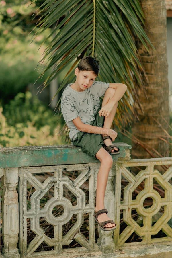 El muchacho se sienta en una cerca fotografía de archivo