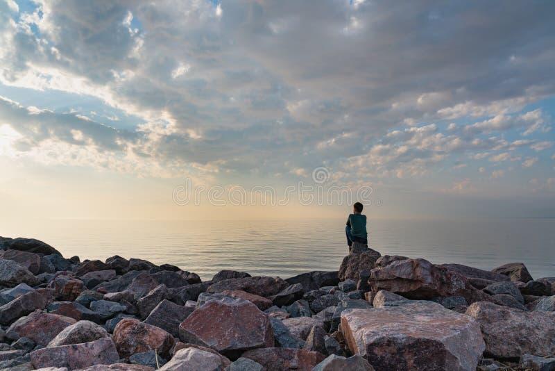 El muchacho se sienta en una playa de piedra en un d?a caliente en la puesta del sol fotos de archivo libres de regalías