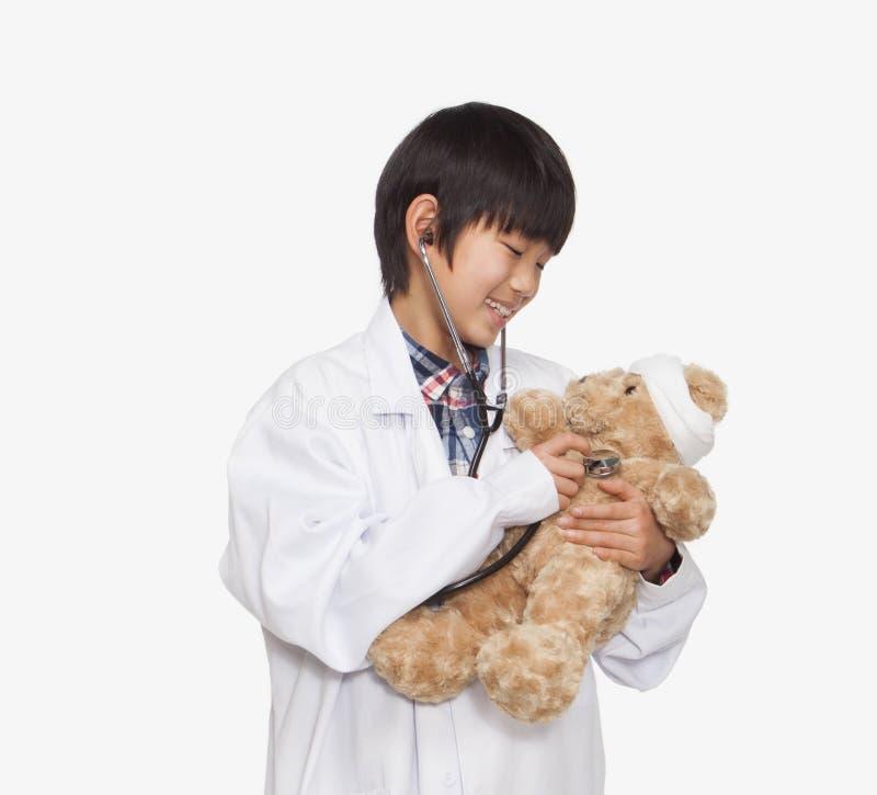 El muchacho se vistió para arriba como doctor que comprobaba las muestras vitales del oso de peluche, tiro del estudio foto de archivo