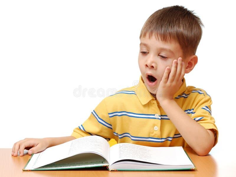 El muchacho soñoliento lee el libro fotos de archivo