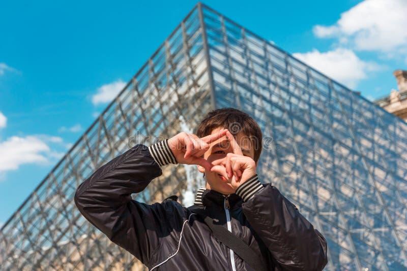 El muchacho sonriente en París enmarca gesticular delante del pyra del Louvre foto de archivo