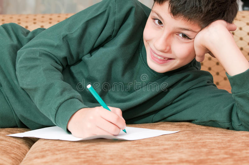 El muchacho sonriente escribe una letra imágenes de archivo libres de regalías