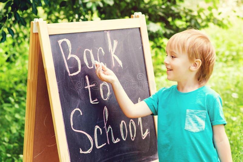 El muchacho sonriente feliz va a enseñar por primera vez De nuevo a escuela El niño escribe en la pizarra Escuela, niño, educació imagenes de archivo
