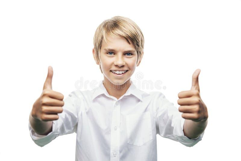 El muchacho sonriente manosea con los dedos para arriba fotografía de archivo libre de regalías
