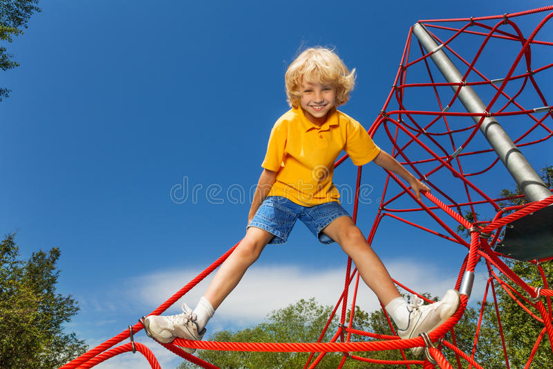 El muchacho sonriente se mantiene aparte en cuerda roja con las piernas foto de archivo libre de regalías