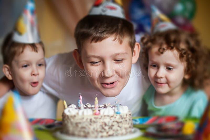 El muchacho sopla hacia fuera las velas en una torta de cumpleaños y abraza su brothe imagen de archivo