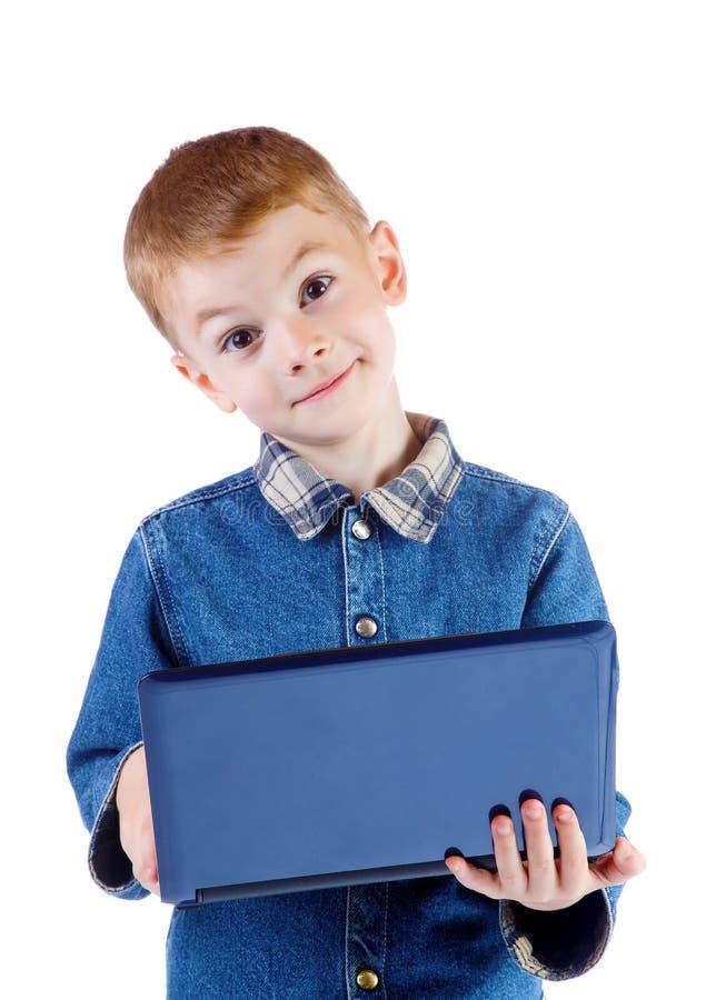 El muchacho sorprendido sostiene el ordenador portátil aislado fotografía de archivo