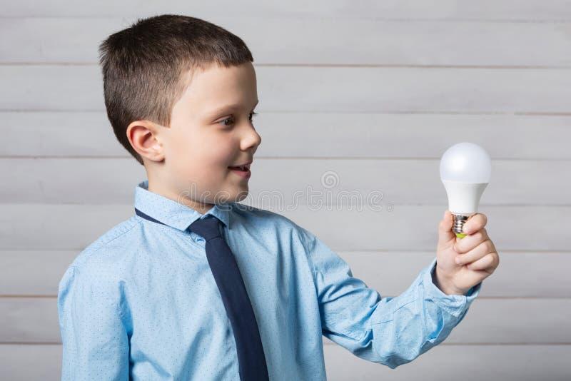 El muchacho sostiene una bombilla en su mano y sonrisas extendidas, concepto de idea fotos de archivo libres de regalías