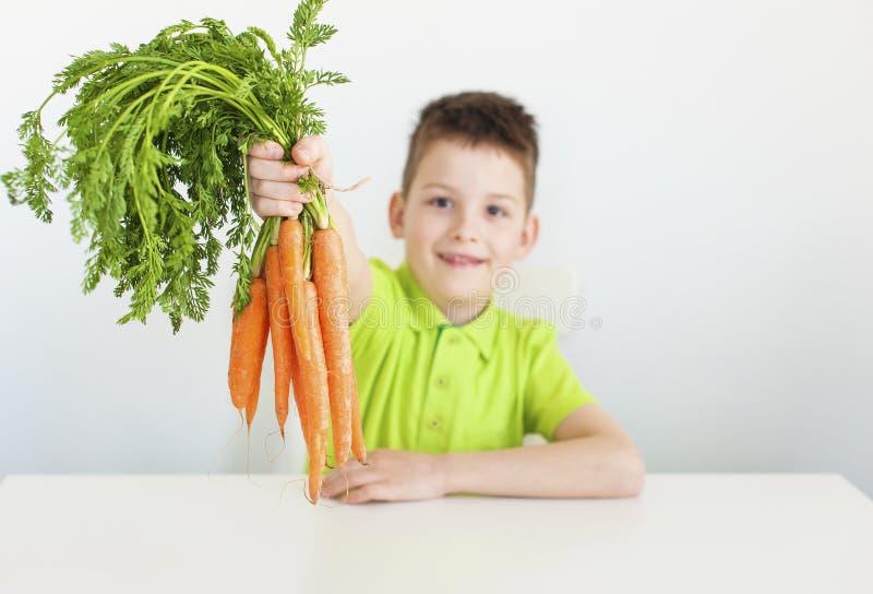 El muchacho sostiene una zanahoria imagenes de archivo