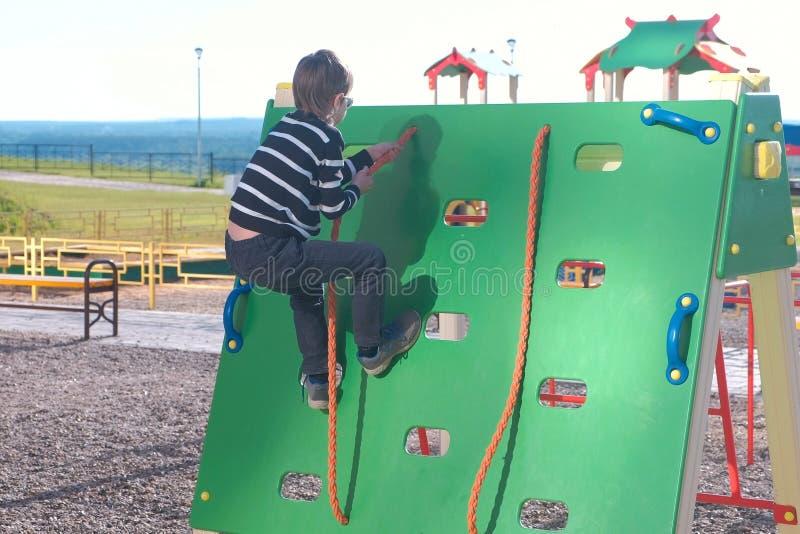 El muchacho sube en una pared que sube que lleva a cabo la cuerda en el patio fotografía de archivo libre de regalías