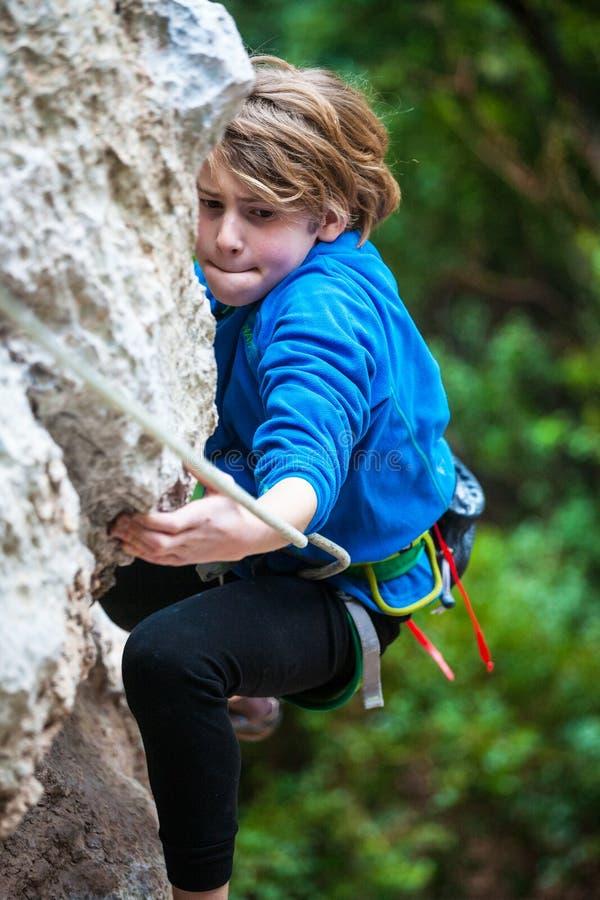 El muchacho sube la roca foto de archivo