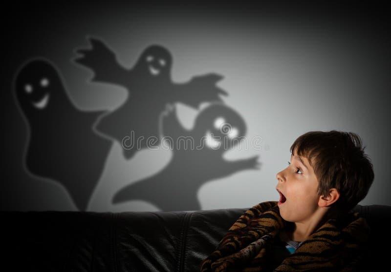 el muchacho tiene miedo de fantasmas en la noche imagen de archivo libre de regalías