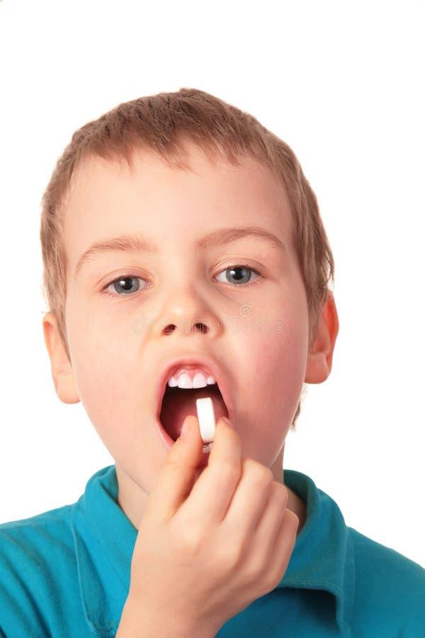 El muchacho traga la píldora foto de archivo
