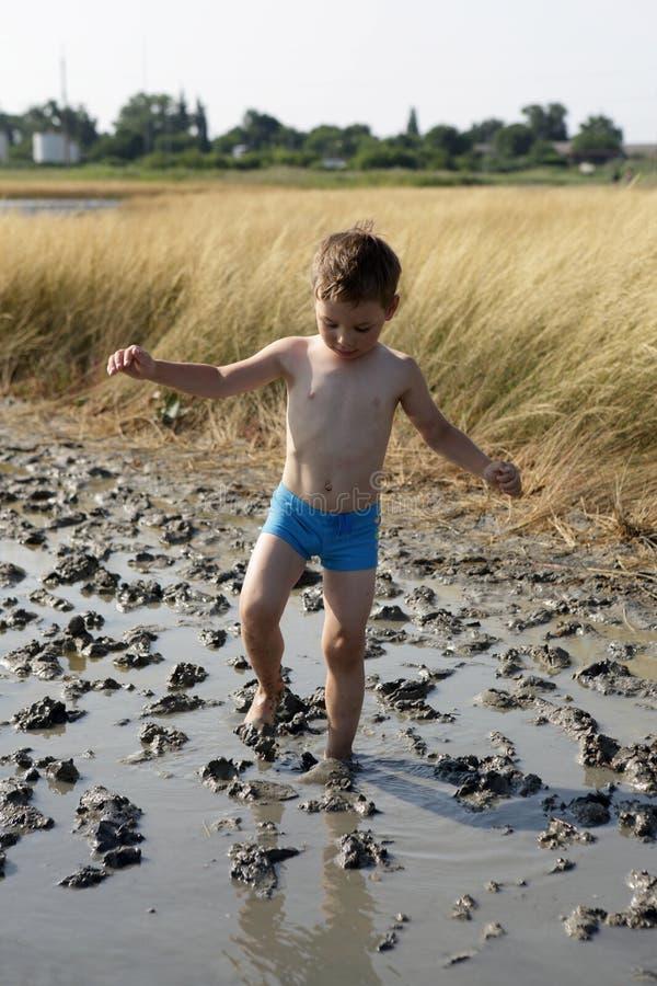 El muchacho va en fango de la cura fotos de archivo