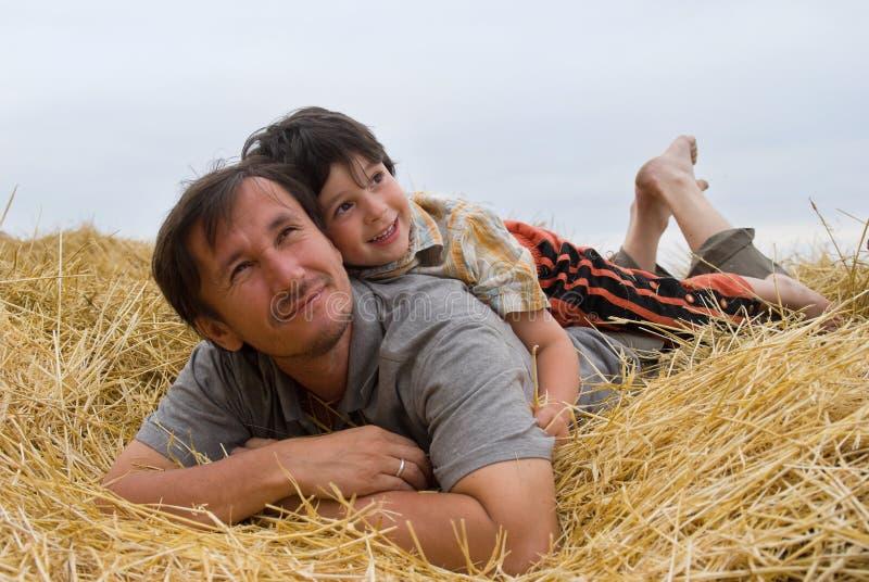 El muchacho y el padre en el heno imagen de archivo libre de regalías