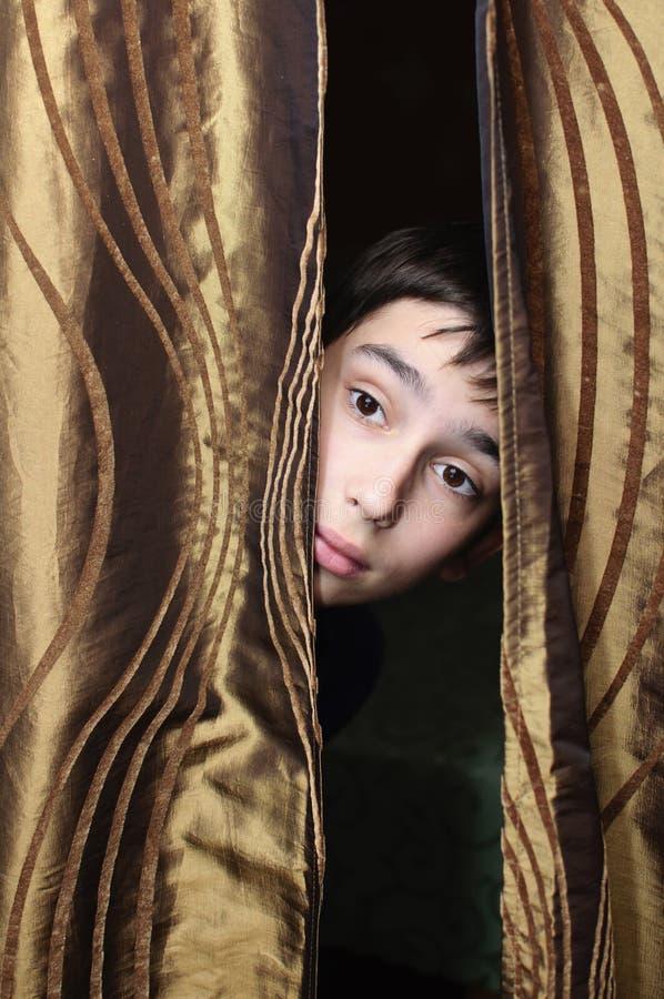 El muchacho y la cortina fotografía de archivo