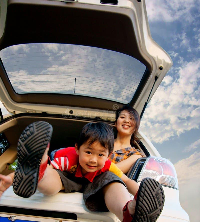 El muchacho y la madre adentro mueven hacia atrás del coche imagenes de archivo