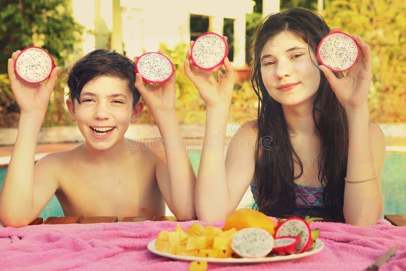 El muchacho y la muchacha del adolescente de los hermanos con el corte del dracon dan fruto fotografía de archivo